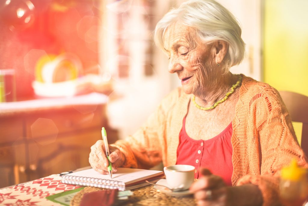 Rentnerin in ihrer Wohnung, schreibend am Tisch