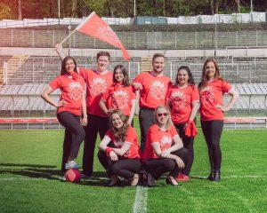 Azubis der Azubi-Filiale 2018 auf Fußballfeld mit Fahne
