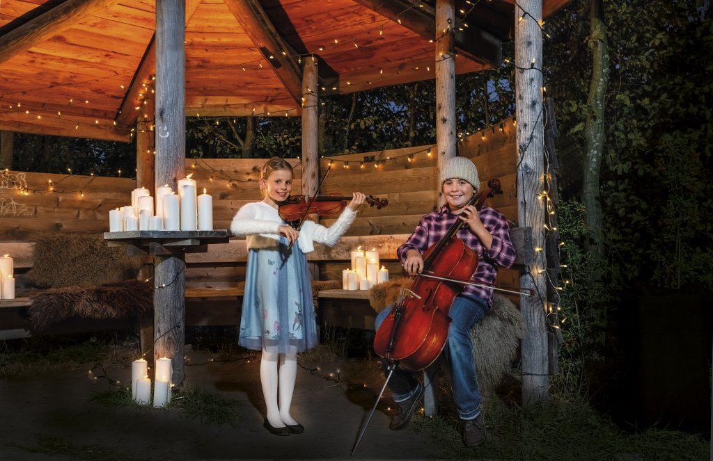 Zwei Kinder der Musikschule musizieren in weihnachtlicher Hütte