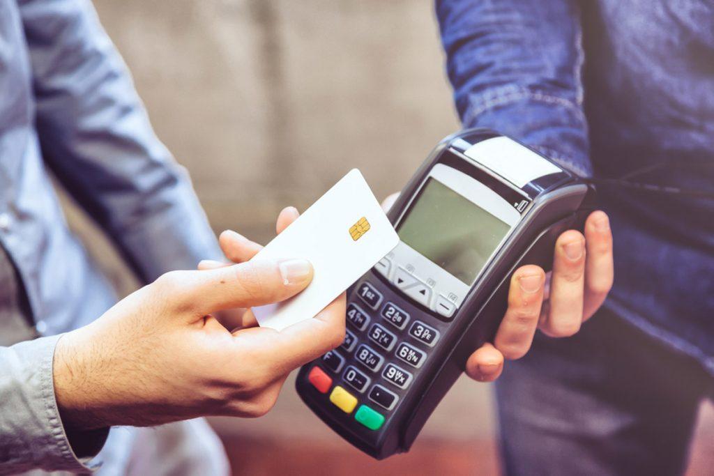 Männerhand hält girocard, um Bargeldlos am Terminal zu bezahlen