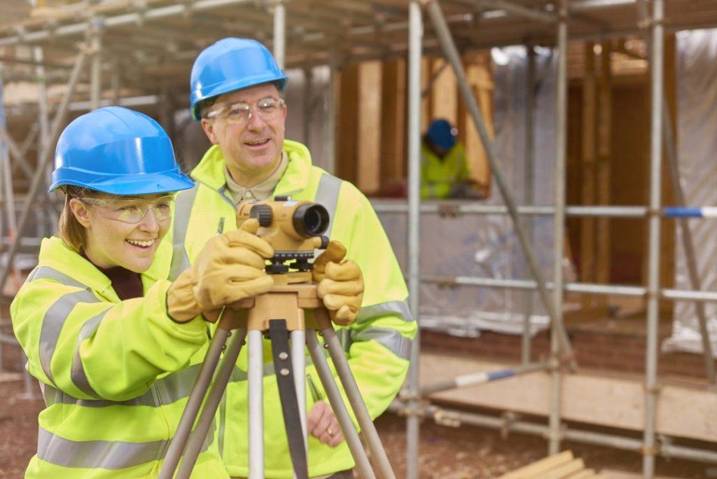 Auszubildende mit ihrem Ausbilder bei der Veremessung einer Baustelle